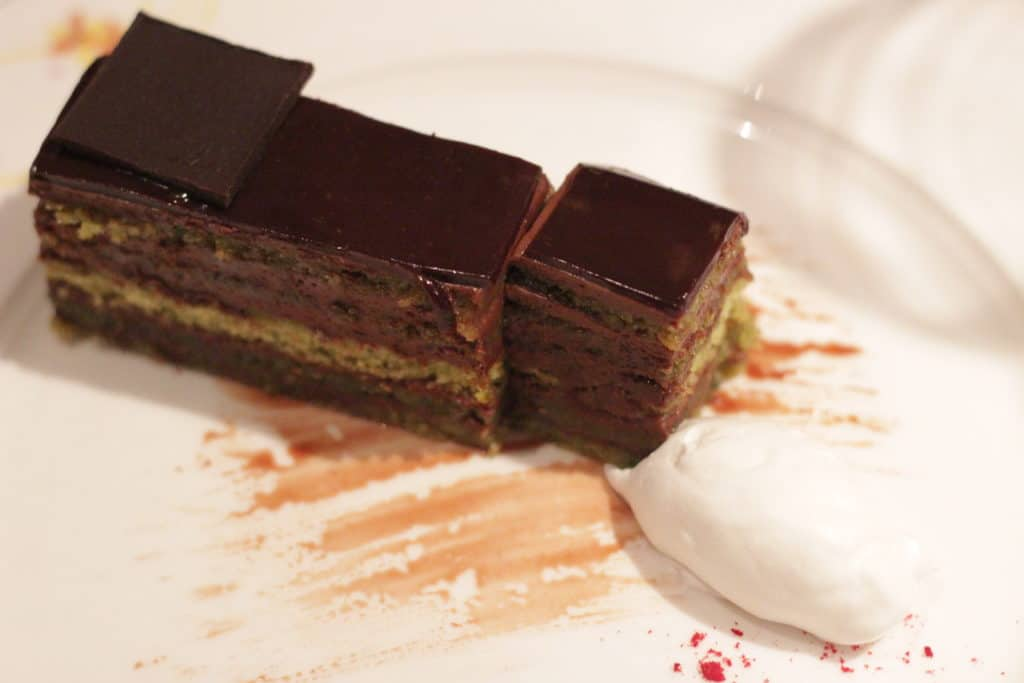Chocolate Indulgence rich Chocolate Cream, layered with Pistachio Chiffon Cake, glazed with Ganache Rapunzel's Royal Table Seasons Menu Westbound Transatlantic Disney Magic